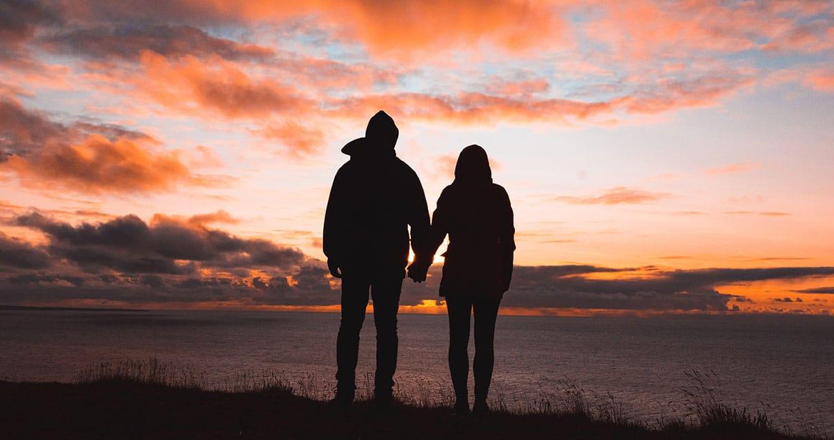 couple qui se tient par la main de dos avec coucher de soleil