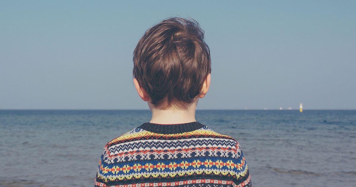 Jeune garçon de dos qui regarde l'océan