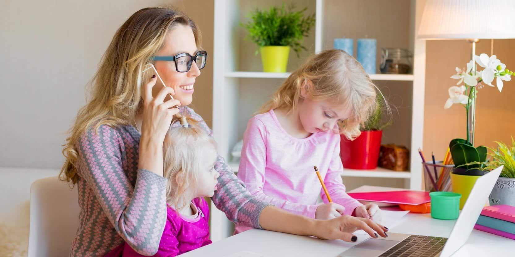 jeune mère de famille avec lunette et chandail rose pâle parlant assise à son bureau, devant son ordinateur portable et parlant au téléphone accompagnée de ses 2 fillettes habillées en rose