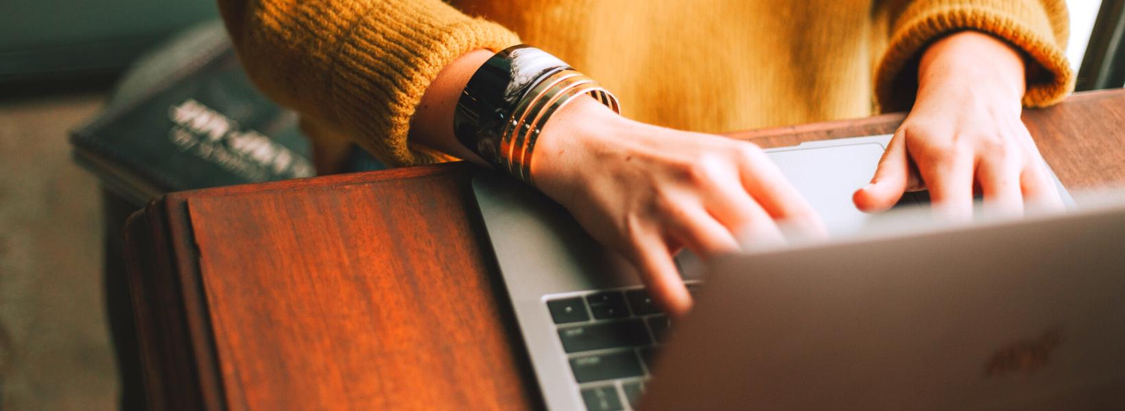 femme gilet orange clavier ordinateur portable