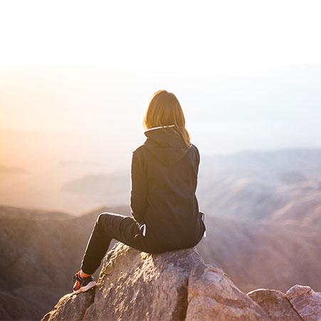 jeune femme assise sur une montagne regardant le lever du soleil à l'horizon