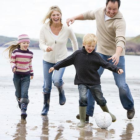 famille qui joue au ballon à la plage