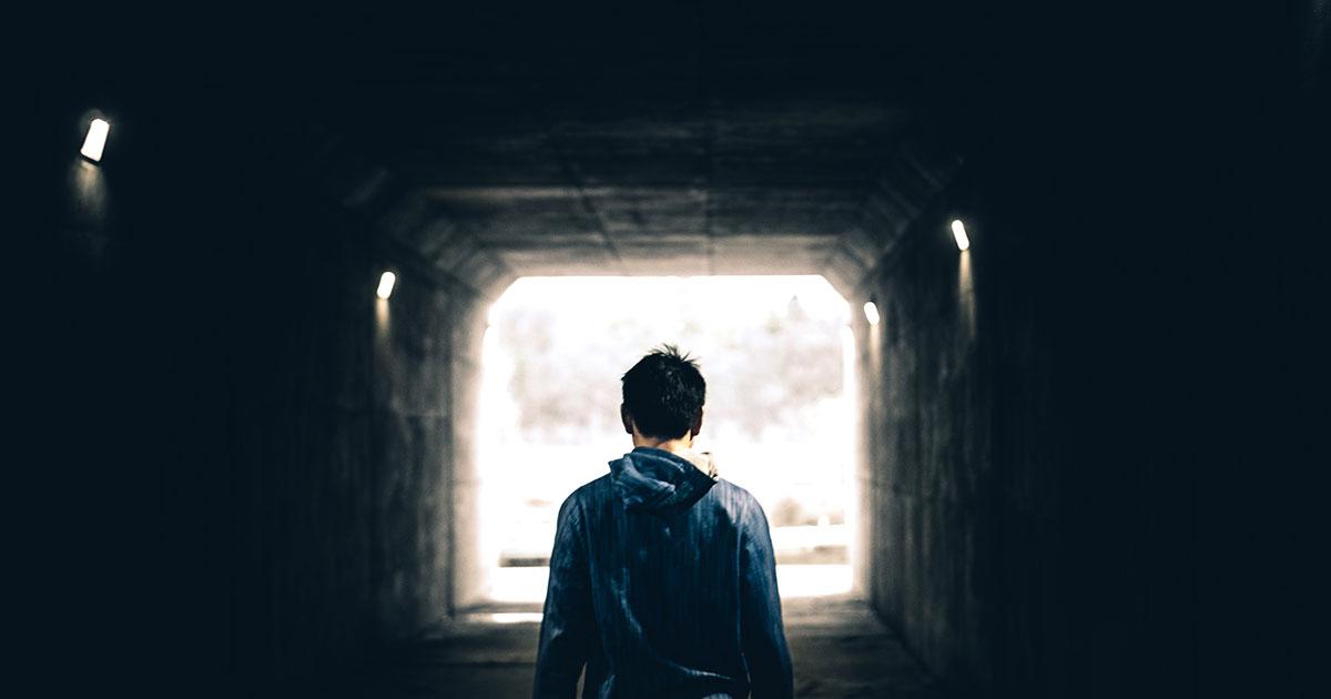 adolescent de dos sous la pluie face à un tunnel sombre