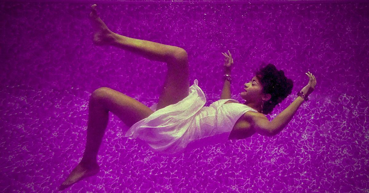 femme portant une robe blanche qui flotte dans une eau mauve